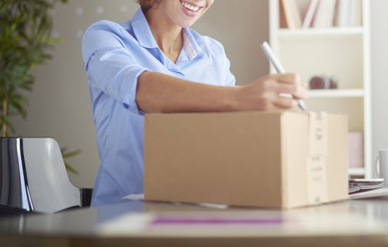 a young woman in her home office looks happy as she labels a small cardboard box for despatch